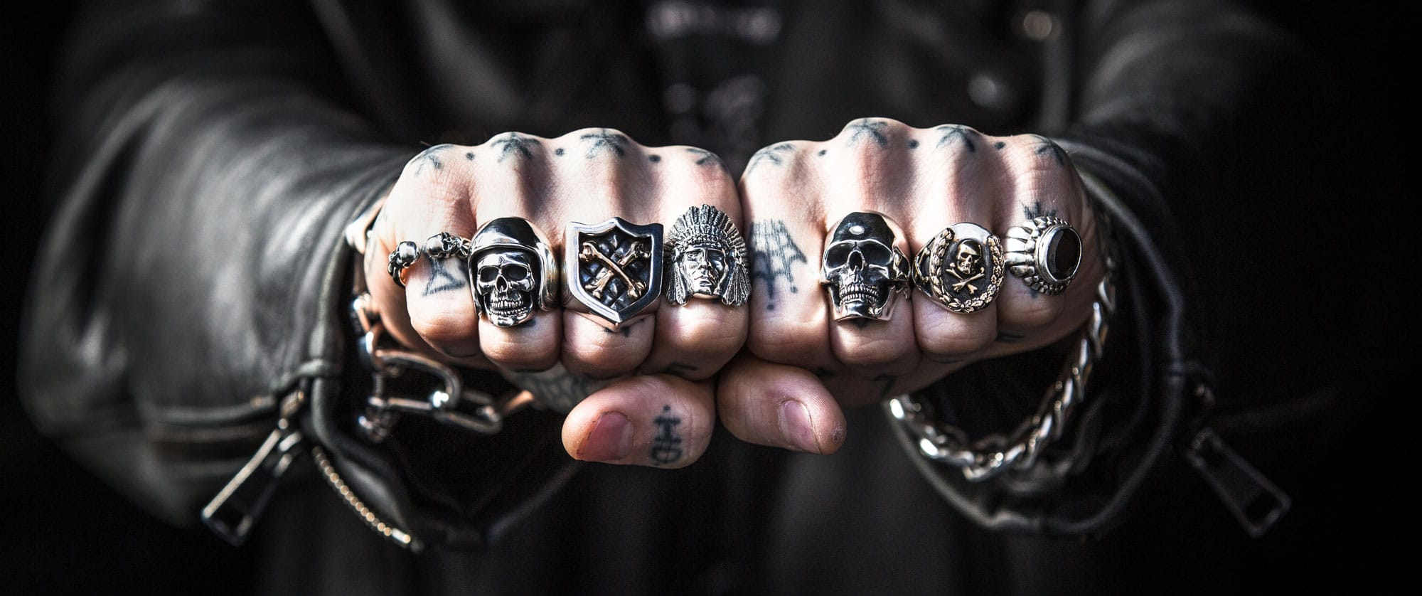 A man in a black leather jacket with hand tattoos wearing lots of silver rings