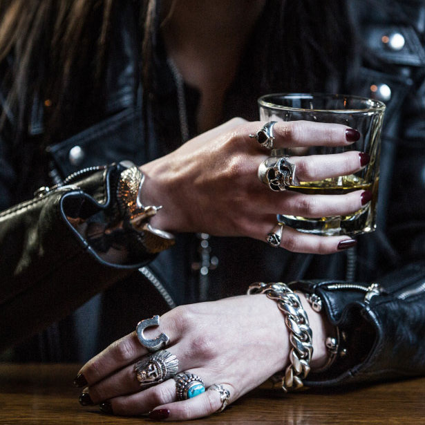 A woman with painted nails wearing a leather jacket and silver jewellery holding a glass of whisky